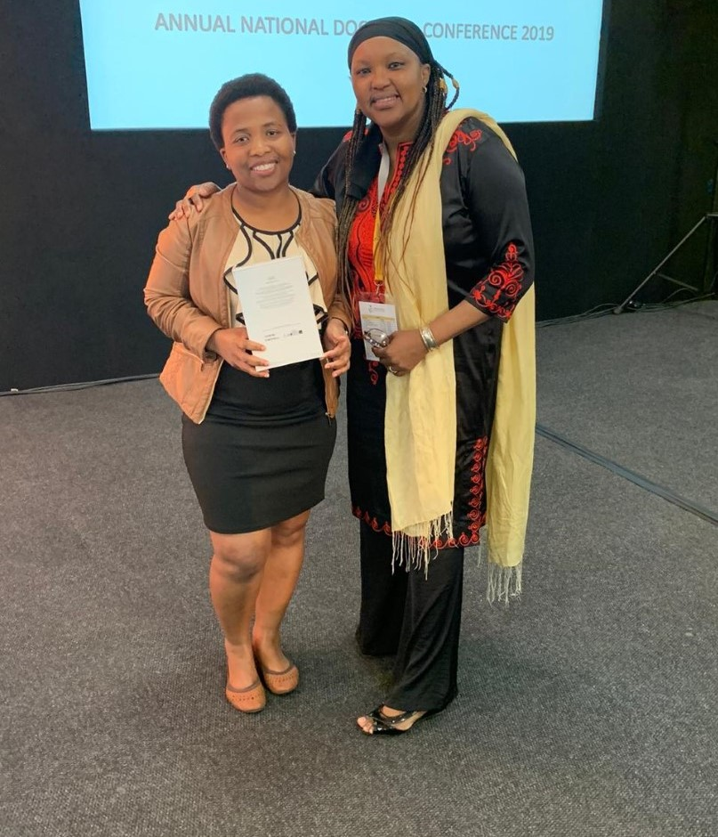 Ms Thembelihle Makhanya (left) receives her award from NIHSS Academic Director, Dr Nthabiseng Motsemme.